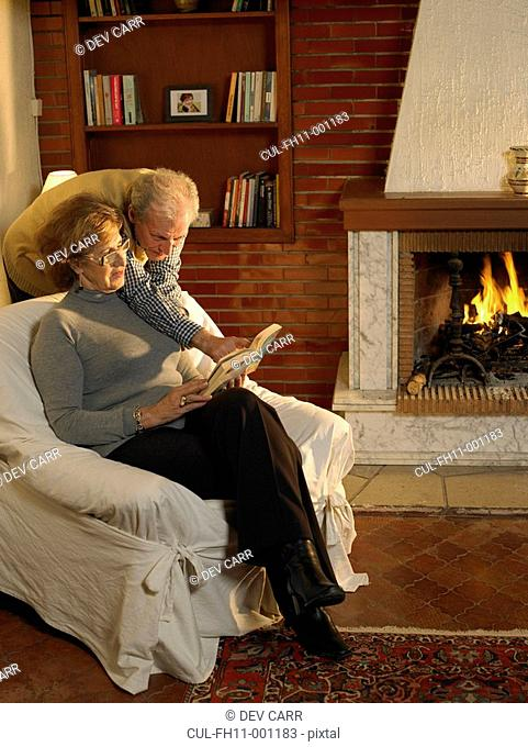Senior couple looking at book in living room