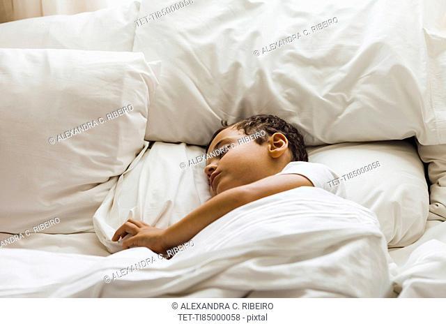 Boy (10-11) sleeping on bed