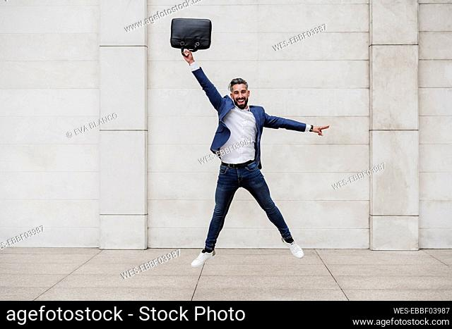 Happy businessman with briefcase jumping on footpath