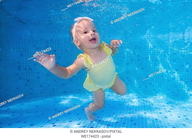 Cheerful little girl in a yellow swimsuit underwater in the pool. Odessa, Ukraine