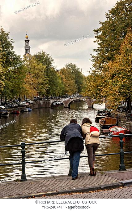 Couple looks at the canal along Prinsengracht with the Westerkerk tower during autumn in Amsterdam