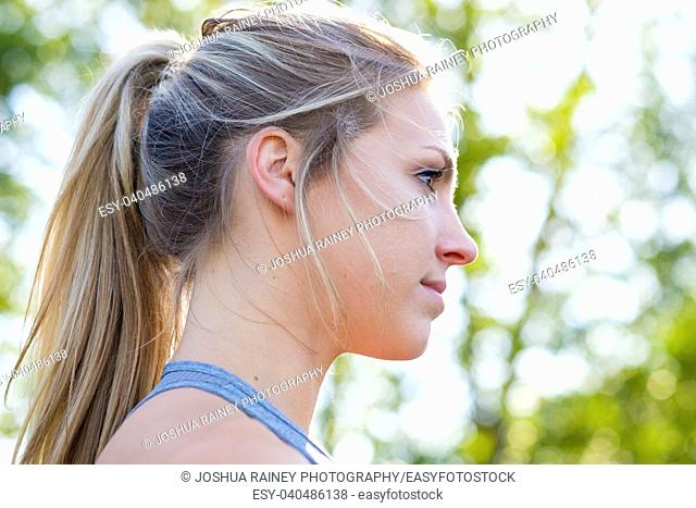 Cute girl with hair up while working out on an outdoor track in the summer