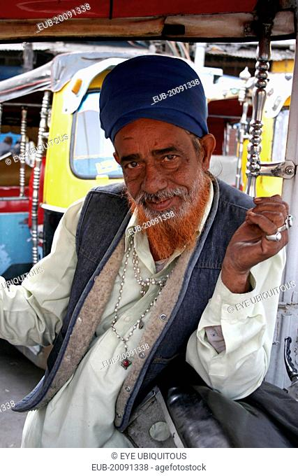 Portrait of auto rickshaw driver inside vehicle with red dyed beard, silver rings and necklace