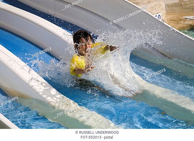 A boy making a splash at the bottom of a water slide
