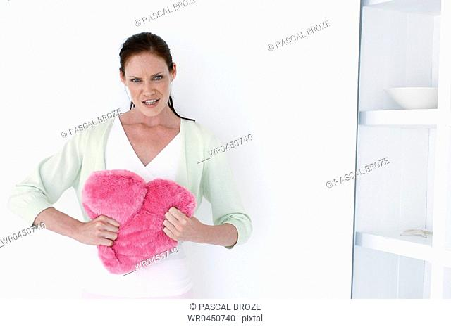 Portrait of a mid adult woman holding a stuffed heart and looking angry