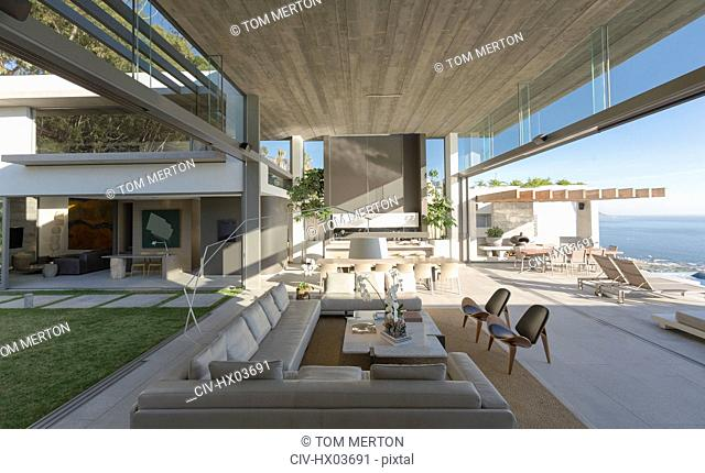 Sunny, open modern, luxury home showcase interior living room with courtyard and ocean view