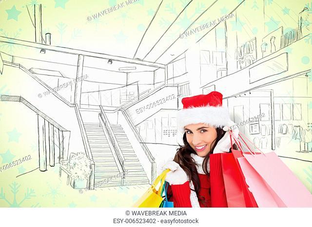 Composite image of festive brunette in winter wear holding shopping bags