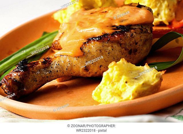 Chicken leg with potatoes closeup