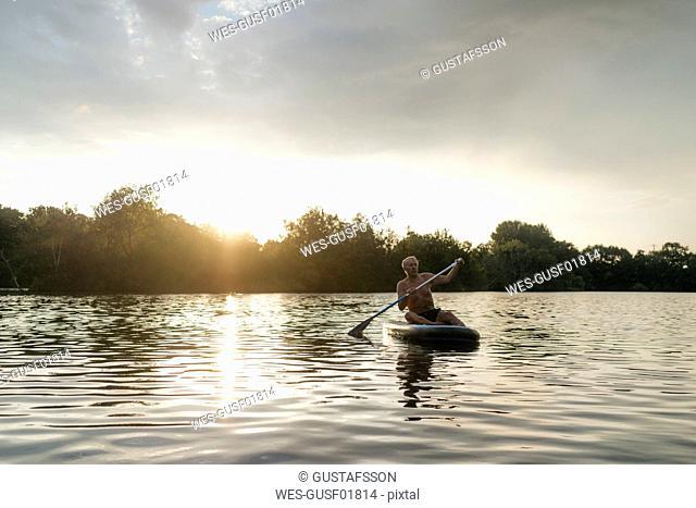 Senior man on SUP board at sunset