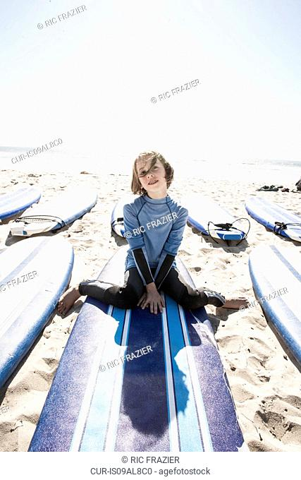 Young surfer on surfboard, Pacific Beach, California, USA