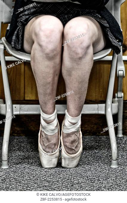 Student in uniform wearing pointe shoes in a classroom
