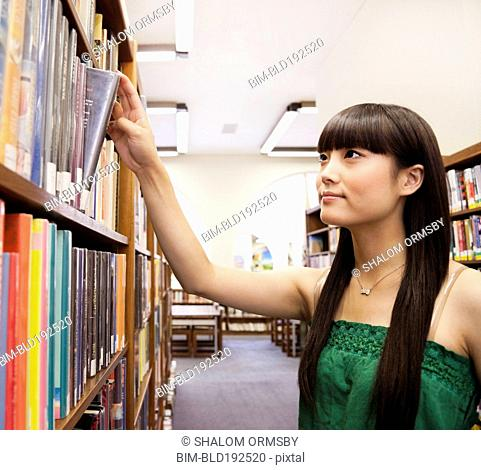 Japanese woman looking for book in library