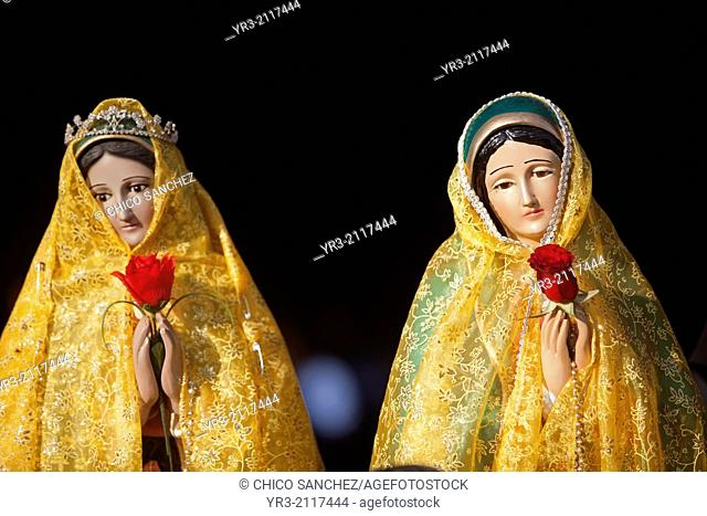 Two sculptures of the Virgin of Guadalupe dressed in yellow clothes and holding red roses are displayed at the pilgrimage to Our Lady of Guadalupe Basilica in...