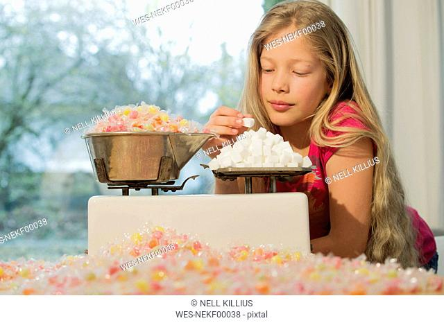Girl behind scales, weighing sugar cubes and a lot of candies