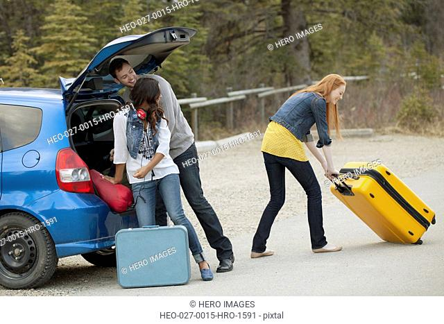 friends unpacking luggage from car
