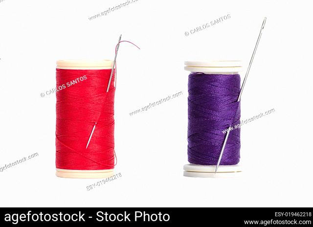 Two red and purple thread bobbin and needle