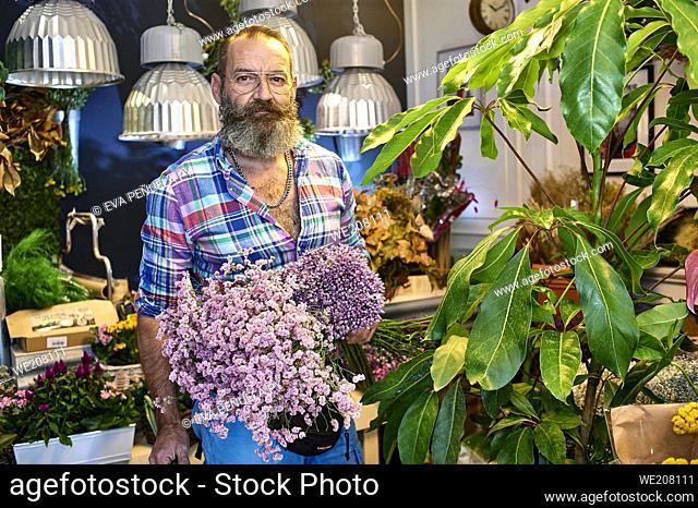 Un florista cuidando varias flores y ramos de flores en su tienda