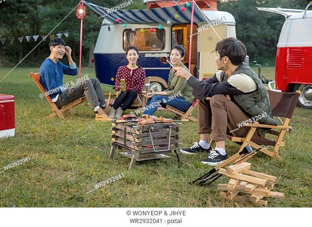Young smiling people enjoying camping