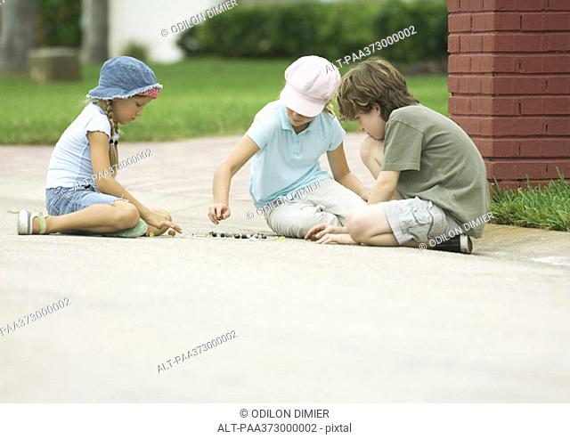 Children playing marbles in street
