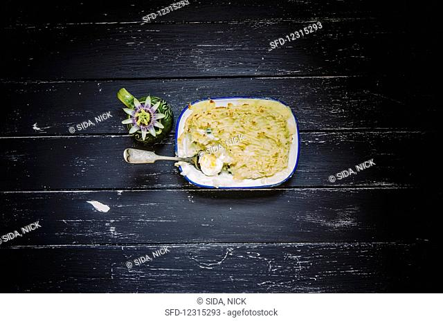 Fish pie with hard boiled eggs in an enamel dish