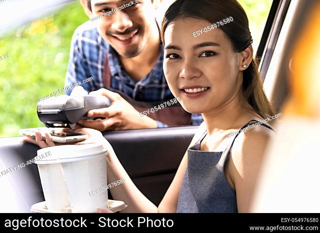 Asian woman customer make mobile payment contactless technology to waiter in drive thru food service while pickup coffee and bakery
