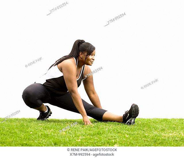 A black plus size female model plus size model in stretching position