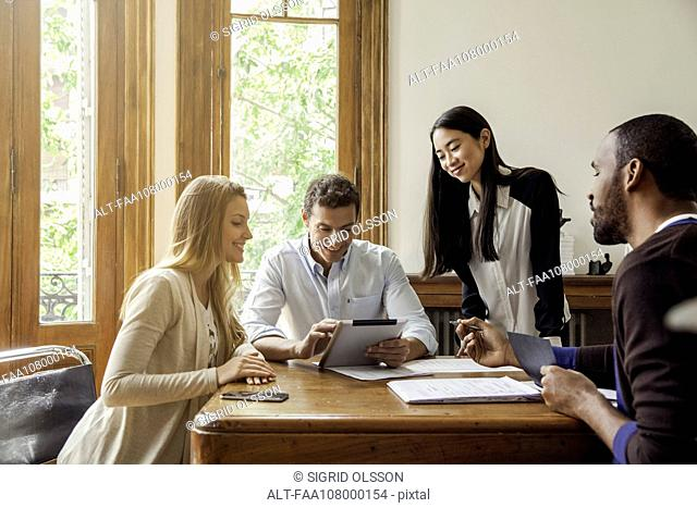 Businessman looking at digital tablet with colleagues in meeting