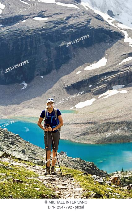 Female hiker on mountain pathway with a colourful alpine lake and mountain cliffs with snow in the background; British Columbia, Canada