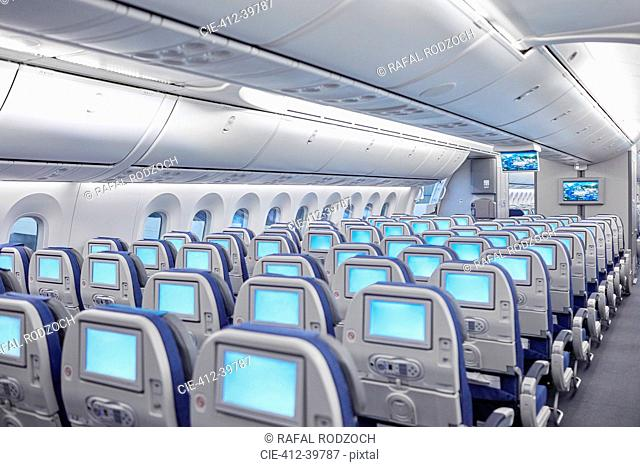 Rows of seats with entertainment screens on airplane