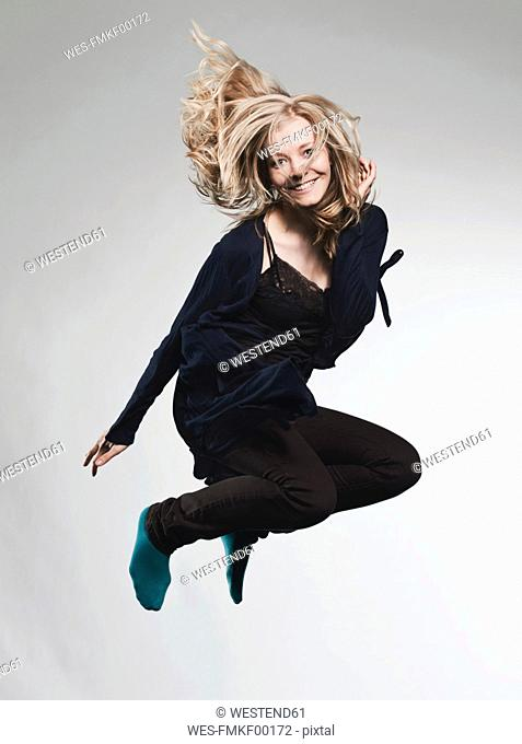 Woman jumping against gray background, smiling, portrait
