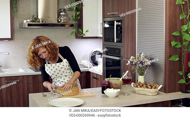 Young happy woman cutting homemade cake in kitchen at home