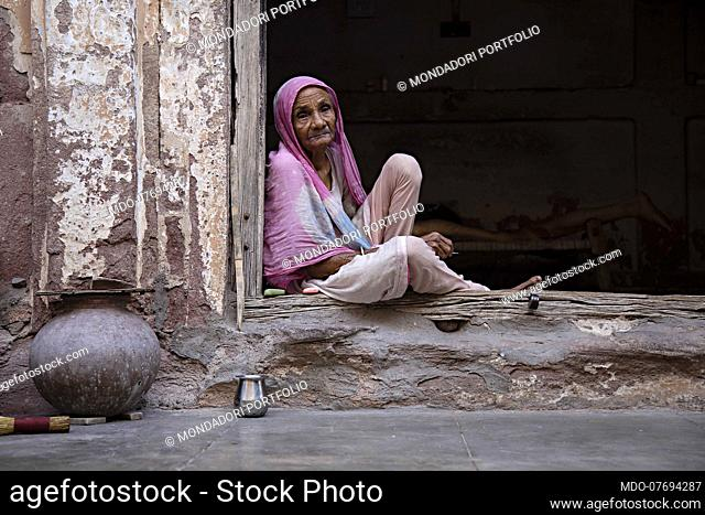 Portrait of a woman sitting leaning on a door. Jodhpur (India), April 17th 2018