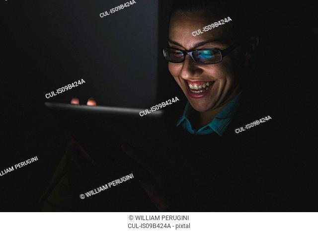 Young woman laughing while using digital tablet touchscreen in darkness