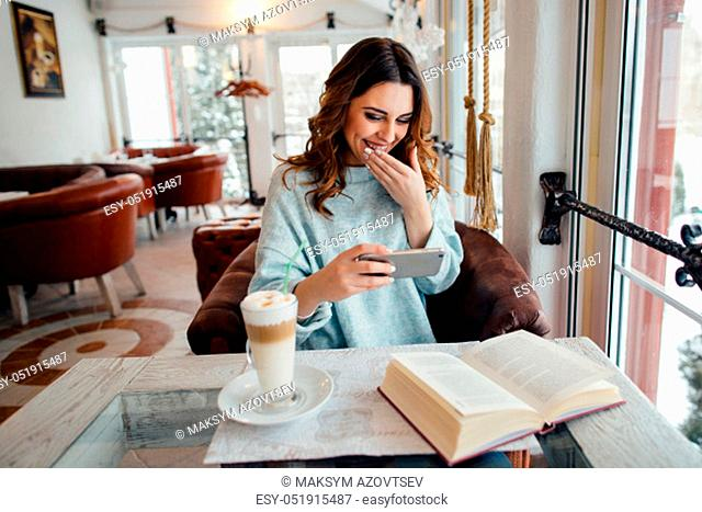 Happy young girl in cafe watching funny video on smart phone and laughing