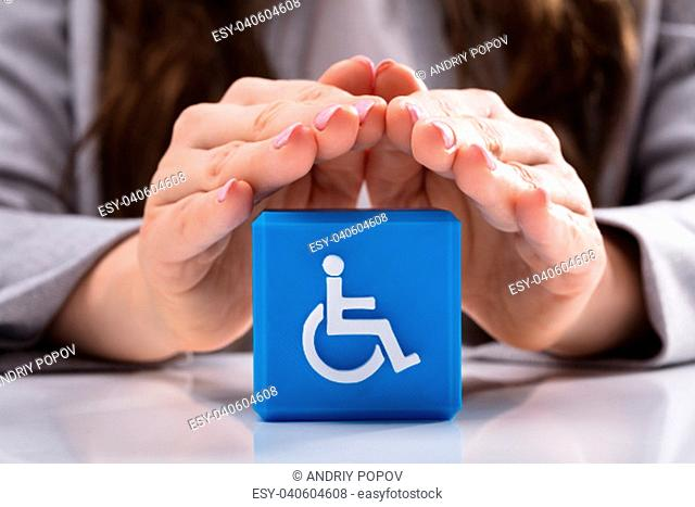 Close-up Of A Woman's Hand Protecting Blue Cubic Block With Disabled Handicap Icon