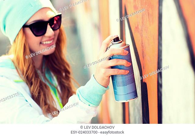 people, art, creativity and youth culture concept - close up of young woman or teenage girl in sunglasses drawing graffiti with spray paint on street wall