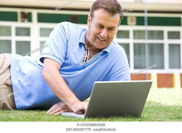 Man lying on lawn of school using laptop