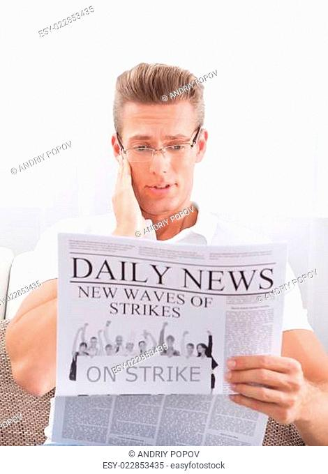 Reading Newspaper With The Headline Strike
