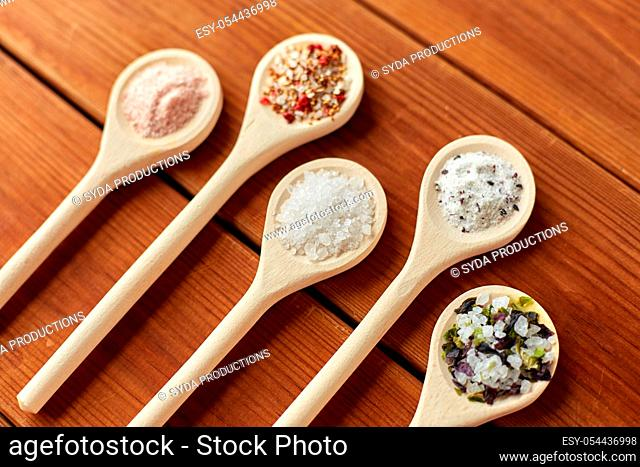 spoons with salt and spices on wooden table