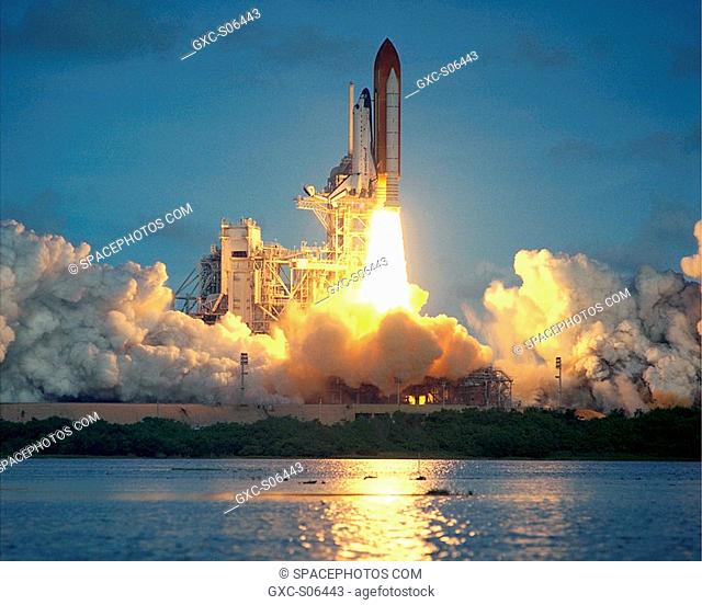09/08/2000 -- Space Shuttle Atlantis's solid rocket boosters trail brilliant flames that light up the clouds of smoke and steam and reflect in the waters Launch...