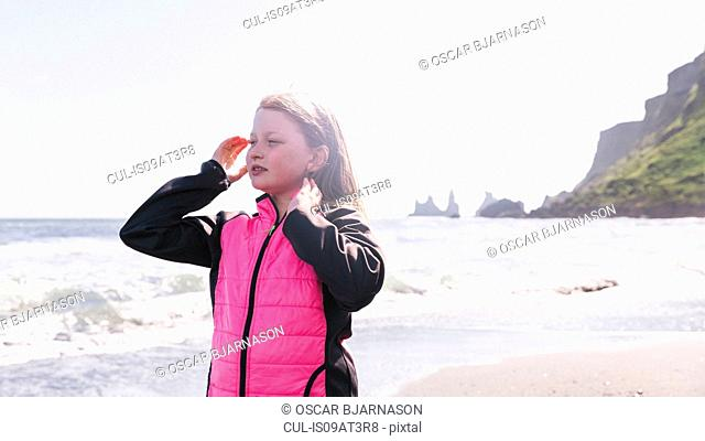 Young girl on beach, looking at view, Vik, Iceland