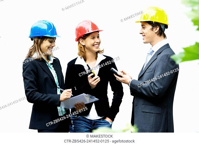 Team of young professionals on a construction site wearing hard hat and using electronic devices