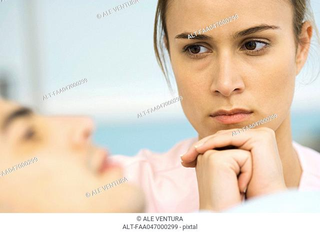 Woman watching sick patient, hands clasped under chin