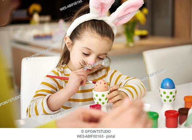 Girl with bunny ears sitting at table painting Easter eggs