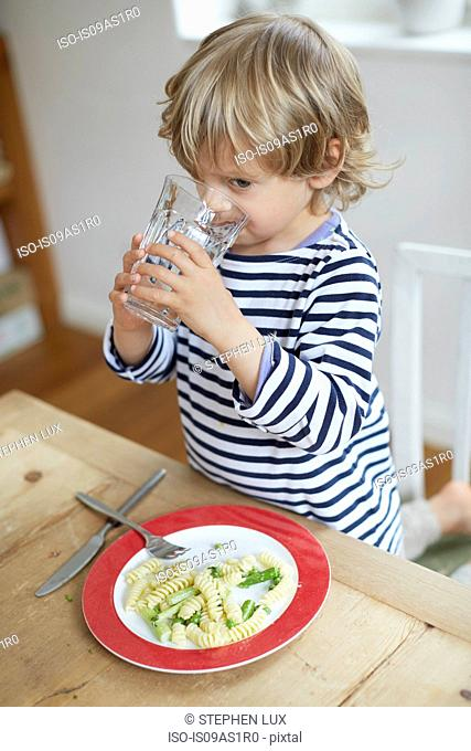 Boy drinking water at dining table