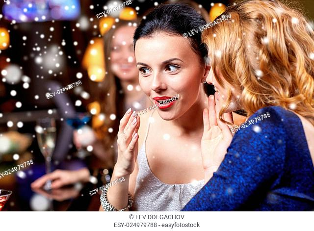 new year, christmas, winter holidays and people concept - happy women gossiping at night club over snow