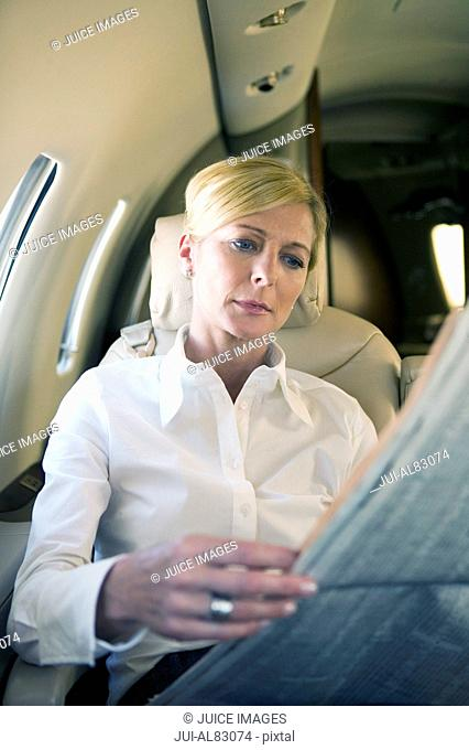 Businesswoman reading newspaper on airplane