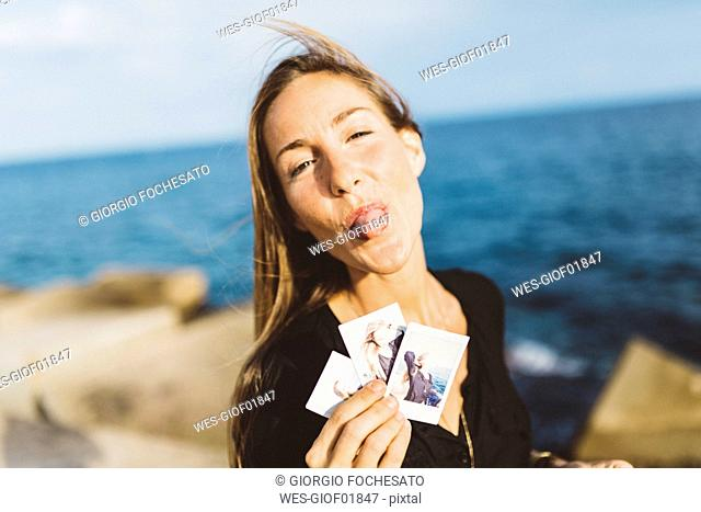 Cheeky young woman showing instant photos of herself at the seafront
