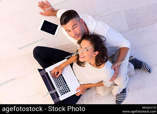 top view of a young couple relaxing at home with tablet and laptop computers reading on the floor