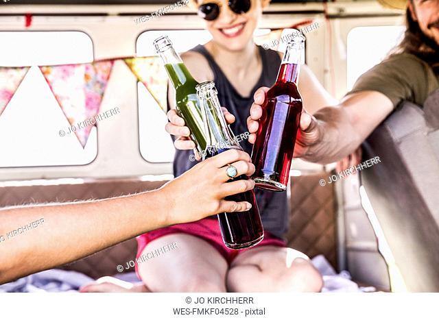 Happy friends inside van clinking bottles